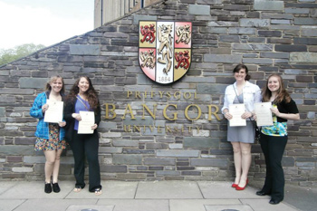Students standing in front of the Bangor University sign.