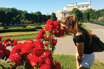 Student enjoying the smell of flowers in Vienna, Austria.